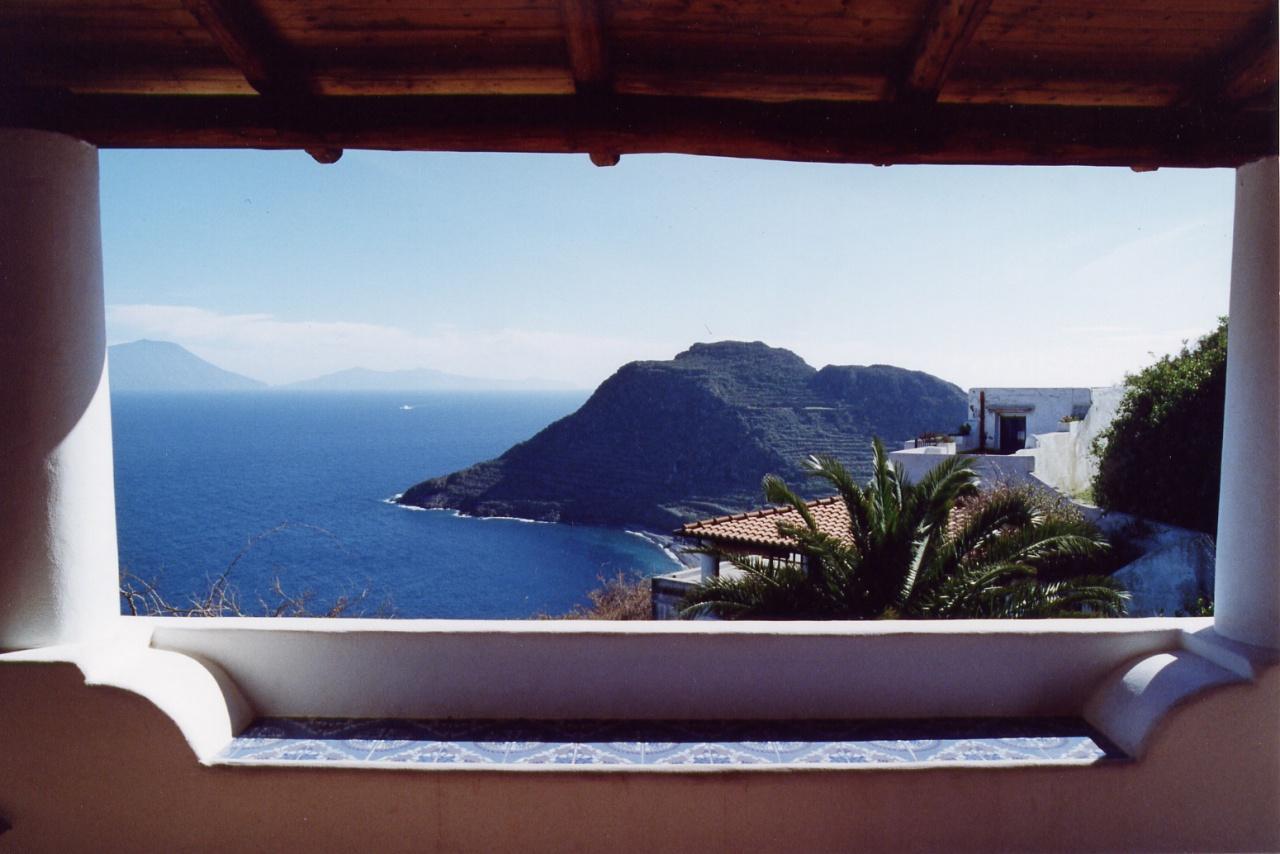 """Una finestra sul mare - Capo Graziano a Filicudi, """"inquadrato"""" da una terrazza eoliana; sullo sfondo le isole di Salina e Lipari"""
